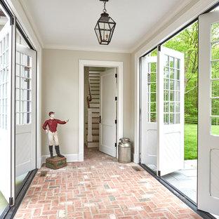 ニューヨークの引き戸トラディショナルスタイルのおしゃれな玄関ホール (グレーの壁、レンガの床、白いドア、ピンクの床) の写真