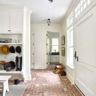 Entryway - traditional brick floor and pink floor entryway idea in New York with white walls and a white front door