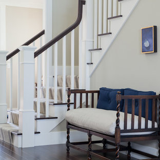 Example of a mid-sized classic dark wood floor and brown floor entryway design in Boston with beige walls and a white front door