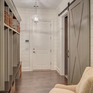 Exemple d'une entrée nature de taille moyenne avec un vestiaire, un mur blanc, un sol en bois foncé et une porte en bois foncé.