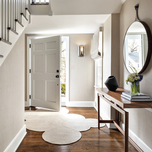 Transitional medium tone wood floor and brown floor entryway photo in New York with gray walls and a white front door