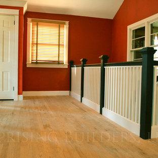 Cette photo montre un très grand hall d'entrée craftsman avec un mur rouge, un sol en bois clair, une porte simple et une porte en bois brun.