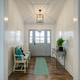 Country medium tone wood floor and brown floor entryway photo in Grand Rapids with white walls and a gray front door