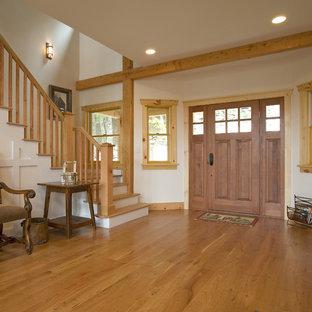 Cette photo montre un hall d'entrée montagne avec un sol en bois brun, une porte simple et une porte en bois brun.