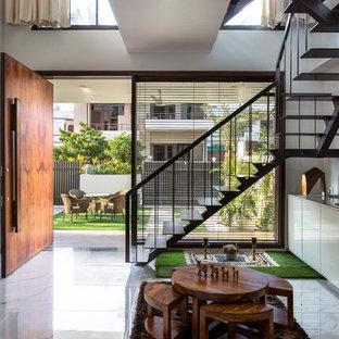 Идея дизайна: фойе в современном стиле с белыми стенами, мраморным полом, поворотной входной дверью, входной дверью из дерева среднего тона и серым полом