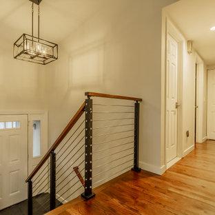 Foto de entrada minimalista con paredes beige, suelo de madera en tonos medios, puerta blanca y suelo marrón