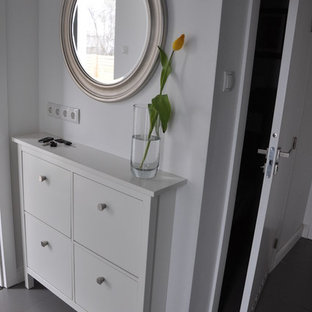 Example of a small minimalist porcelain floor foyer design in Other with white walls