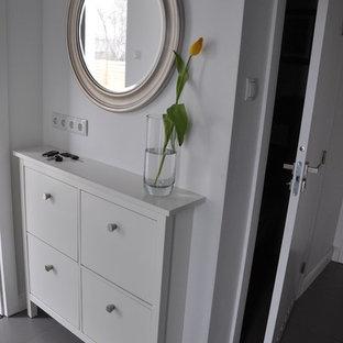Foto på en liten funkis foajé, med vita väggar och klinkergolv i porslin