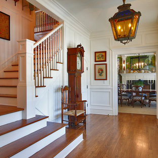 Foyer - traditional medium tone wood floor foyer idea in New York with a glass front door