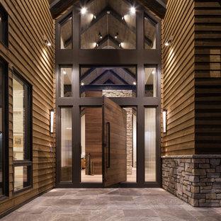 Foto på en mycket stor funkis ingång och ytterdörr, med en pivotdörr, mörk trädörr, ljust trägolv och brunt golv