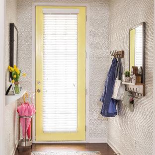 アトランタの中サイズの片開きドアコンテンポラリースタイルのおしゃれな玄関ロビー (黄色い壁、濃色無垢フローリング、黄色いドア、茶色い床) の写真