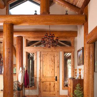 Idee per un grande ingresso rustico con pavimento in cemento, una porta singola, una porta in legno chiaro e pareti beige