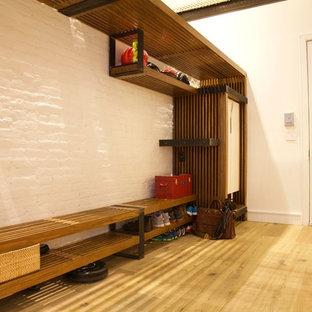 Diseño de hall industrial con paredes blancas, suelo de madera clara, puerta simple y puerta blanca