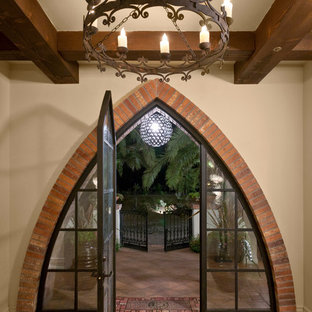Example of a tuscan terra-cotta floor entryway design in Other with beige walls and a glass front door