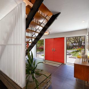 Cette photo montre un grand hall d'entrée rétro avec un mur gris, un sol en ardoise, une porte double, une porte rouge et un sol gris.