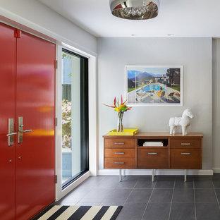 50 tals inredning av en stor foajé, med en dubbeldörr, grå väggar, skiffergolv, en röd dörr och grått golv