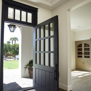 Bild på en stor vintage ingång och ytterdörr, med vita väggar, mellanmörkt trägolv, en enkeldörr, en svart dörr och brunt golv