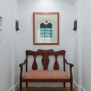 Idées déco pour un hall d'entrée campagne de taille moyenne avec un mur blanc, un sol en bois brun, une porte simple, une porte blanche et un sol marron.