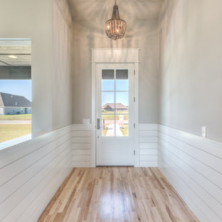 Mid-sized cottage medium tone wood floor and brown floor entryway photo in Other with gray walls and a white front door