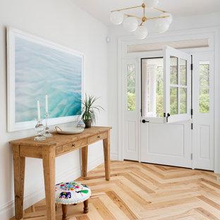 Imagen de distribuidor marinero con paredes blancas, suelo de madera clara, puerta tipo holandesa, puerta blanca y suelo beige