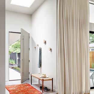 Foto på en funkis farstu, med vita väggar, ljust trägolv, en enkeldörr och en grå dörr