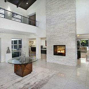 Réalisation d'une grand entrée minimaliste avec un couloir, un mur blanc, un sol en marbre, une porte double, une porte en verre et un sol blanc.