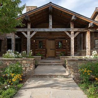 Réalisation d'une porte d'entrée chalet avec un mur marron, une porte simple, une porte en bois brun et un sol beige.