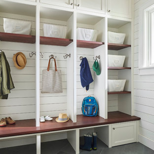 Inspiration for a beach style gray floor mudroom remodel in Boston with white walls