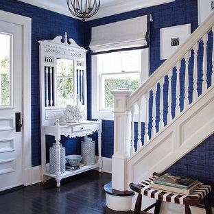 Ispirazione per un ingresso costiero con pareti blu, parquet scuro, una porta singola e una porta bianca