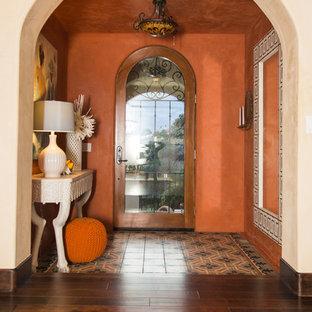Idee per un corridoio mediterraneo di medie dimensioni con pareti arancioni, parquet scuro, una porta singola, una porta in vetro e pavimento marrone