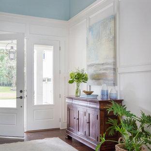 Klassische Haustür mit blauer Wandfarbe, braunem Holzboden, Einzeltür, weißer Tür und braunem Boden in Jacksonville