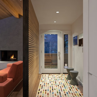 Small minimalist medium tone wood floor entryway photo in Portland with white walls and a glass front door