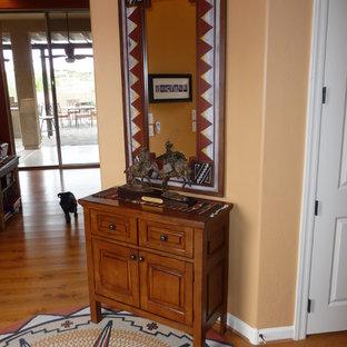 Неиссякаемый источник вдохновения для домашнего уюта: фойе среднего размера в стиле фьюжн с оранжевыми стенами, светлым паркетным полом и коричневым полом