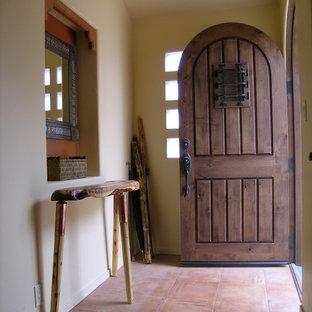 Foto di una piccola porta d'ingresso stile americano con pavimento in terracotta, una porta singola, una porta in legno scuro e pareti beige