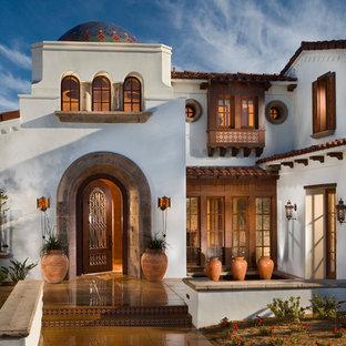 На фото: входная дверь в средиземноморском стиле с белыми стенами, одностворчатой входной дверью, входной дверью из дерева среднего тона, желтым полом и бетонным полом