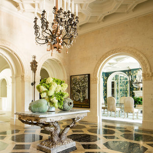 Tuscan multicolored floor foyer photo in Dallas with beige walls
