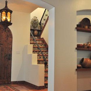 オースティンの中くらいの片開きドアサンタフェスタイルのおしゃれな玄関ロビー (白い壁、テラコッタタイルの床、濃色木目調のドア) の写真