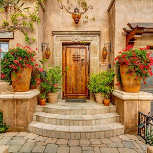 Large southwest entryway photo in San Diego with beige walls and a dark wood front door