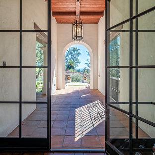 サンタバーバラの広い片開きドア地中海スタイルのおしゃれな玄関ドア (白い壁、セラミックタイルの床、ガラスドア、赤い床) の写真