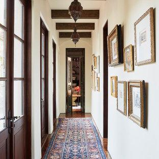 Пример оригинального дизайна: огромная узкая прихожая в средиземноморском стиле с белыми стенами, темным паркетным полом, двустворчатой входной дверью, входной дверью из темного дерева и коричневым полом