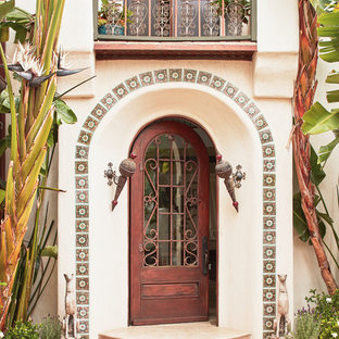 Inspiration for a mid-sized mediterranean entryway remodel in Los Angeles with a dark wood front door and white walls