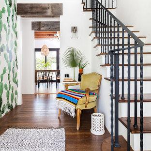 Mediterraner Eingang mit weißer Wandfarbe, braunem Holzboden, braunem Boden und Korridor in Sacramento