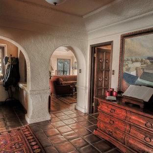 Entryway - large mediterranean terra-cotta tile and brown floor entryway idea in Los Angeles with beige walls and a dark wood front door
