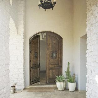 Modelo de puerta principal ladrillo, mediterránea, grande, con paredes blancas, suelo de piedra caliza, puerta doble, puerta de madera oscura, suelo beige y ladrillo