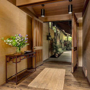 Inspiration for a large asian medium tone wood floor and brown floor entryway remodel in Seattle with brown walls and a medium wood front door