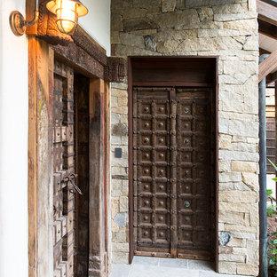 Inspiration for a tropical front door in Cairns with white walls, a double front door, a dark wood front door and grey floor.