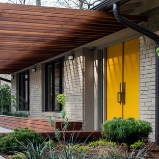 Cette photo montre une porte d'entrée rétro avec un mur beige, béton au sol, une porte double, une porte jaune et un sol gris.