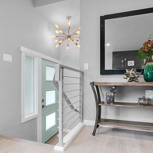 シアトルの片開きドアコンテンポラリースタイルのおしゃれな玄関 (グレーの壁、淡色無垢フローリング、緑のドア) の写真