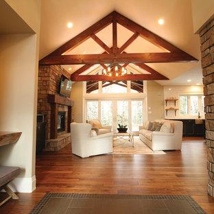 Cette image montre un grand hall d'entrée chalet avec un sol en bois brun, une porte pivot et une porte en bois brun.