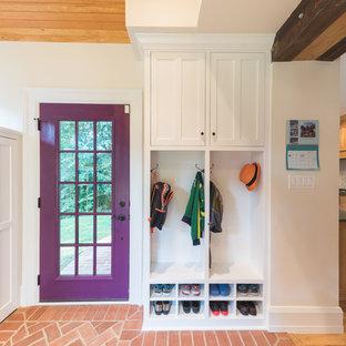 Ejemplo de vestíbulo posterior tradicional con paredes blancas, suelo de ladrillo, puerta simple, puerta violeta y suelo rojo